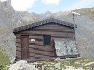 """Una originale struttura esterna, che contiene pietre, serve a realizzare una camera d'aria calda per """"riscaldare"""" naturalmente l'interno del bivacco."""